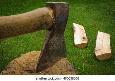 the axe which is sticking out of a stub has split firewood/the axe has split firewood