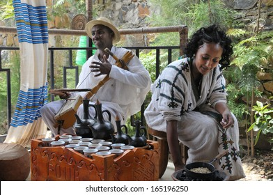 Axum, Ethiopia - September 28, 2012: Young woman in traditional clothing is preparing a coffee ceremony. Man is playing on a masenqo. This ceremony is an important part of the Ethiopian culture.