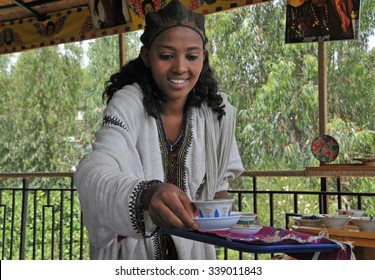 Axum, Ethiopia - September 28, 2012: Young Ethiopian woman in traditional clothing is serving coffee during a traditional coffee ceremony. This ceremony is an important part of the Ethiopian culture.