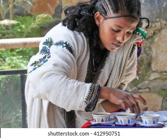Axum, Ethiopia - September 28, 2012: Young Ethiopian woman in traditional clothing is serving coffee during a traditional coffee ceremony.