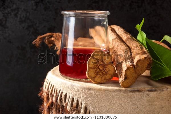 Ayahuasca brew with baniseriopsis caapi mimosa hostilis rootbark and chackruna leaves on shamanic drum.