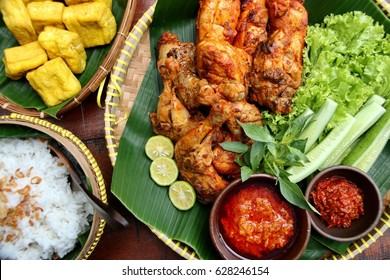 Ayam Bakar. Indonesian char-grilled chicken. Arranged on bamboo tray lined with banana leaf. Served with extra spice paste, chili paste, fresh green vegetables, fried tofu and steamed rice.