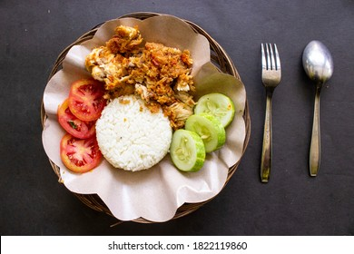 ayam geprek or chicken crush or chicken smashed is indonesian food made from made fried chicken pounded with chilli and garlic flavour and served with vegetables and rice