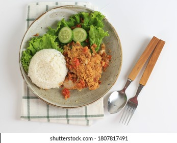 Ayam Geprek is Popular Street Food in Indonesia. Made from Crispy Chicken Smashed in Sambal Bawang (Chilli Garlic Sauce) . Served with Rice and Vegetable