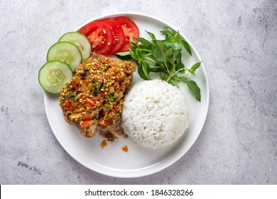 Ayam Geprek is Popular Street Food in Indonesia. Made from Crispy Chicken Smashed in Sambal Bawang (Chilli Garlic Sauce) . Served with Rice and Vegetable. Top view.