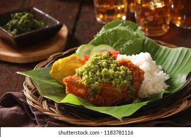 Ayam Geprek Sambal Andaliman. Popular fusion dish of smashed southern fried chicken with topping of andaliman relish from Batak cuisine. Accompanied with cassava leaf stew.