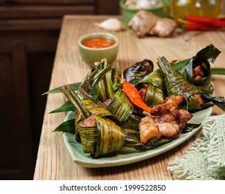 """""""Ayam Goreng Daun Pandan"""" or Fried chicken wrapped in pandan leaves, serving on wooden table  with chilli sambal or chilli sauce. Indonesian food and cuisine. Thailand authentic food and cuisine."""