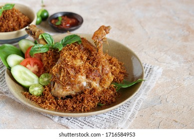 Ayam Goreng Kelapa Parut or Chicken fried with coconut shredded with tomato and cucumber, Indonesian traditional food, served in brown ceramic plate. Selective focus.