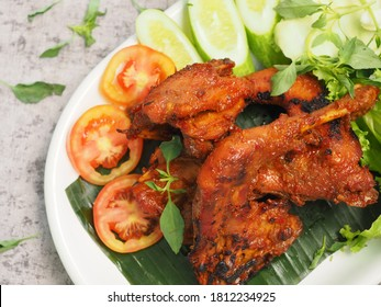 Ayam kampung bakar bumbu rempah, a free range grilled chicken, seasoned and full of spices , Indonesian Traditional dish. serving on white plate and with sambal.