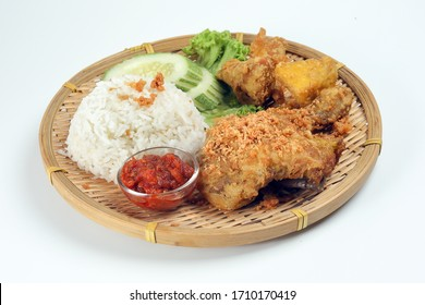 Ayam penyet a East Javanese cuisine smashed fried chicken dish with floss sambal slices of cucumbers fried tofu and tempeh
