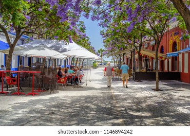 Ayamonte, Spain - June 20 2018.  Tourists and locals enjoy the shade of the pretty jacaranda  trees on Plaza La Lota. Some of them are alfresco dining other are strolling along the pedestirian area.