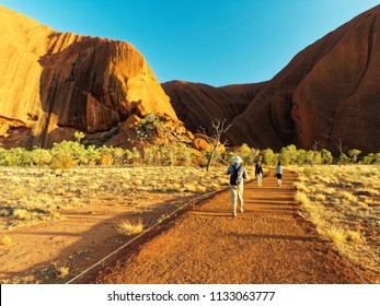 Ayers Rock,  The Red Centre of Central Australia,, Northern Territory. September 2017 Tourist on an early Uluru Base Walk with morning light from a rising Sun.