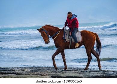 Ayia Eirini, Cyprus - 24 March, 2019: Man riding on a brown galloping horse on Ayia Erini beach in Cyprus against a rough sea