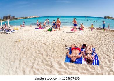 AYIA NAPA, CYPRUS - APRIL 07, 2018: People laying on the beach