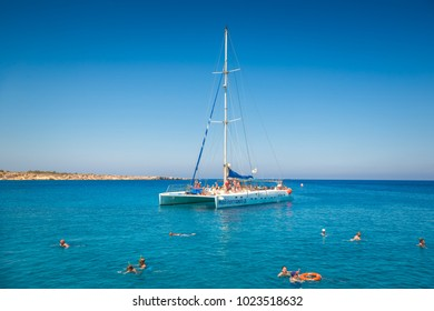 AYIA NAPA, CYPRUS - JULY 16, 2016: Catamaran loaded with tourists in the waters of the Mediterranean near Cape Greco.