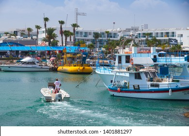 Ayia Napa, Cyprus - June 12, 2018: Ayia Napa resort town at the far eastern end of the southern coast of Cyprus island.  Small pleasure boat enters the port, tourists walk on coast