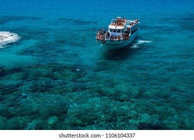AYIA NAPA, CYPRUS, JUNE 15, 2017: Tourist boat approaching the sea caves of Ayia Napa from the sea. The littoral caves are one of the major tourist attractions of the island of Cyprus