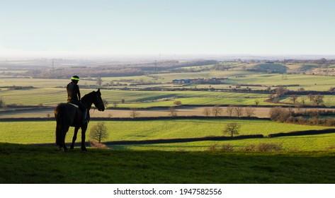 AYLESBURY, UK - December 13, 2014. Woman riding horse in landscape, horseback riding on a hill overlooking Aylesbury Vale, Buckinghamshire, UK