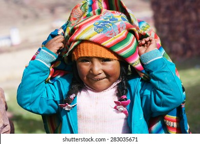 aymara girl playing with traditional cloth