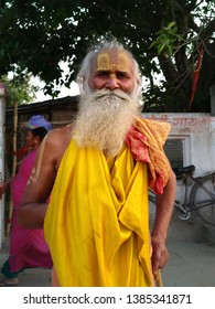 Ayodhya Uttar Pradesh/India - April 28, 2019. Portrait of Old Indian monk sadhu Baba Nondo. Beard sadhu with yellow clothes, painted forehead poses for the camera.