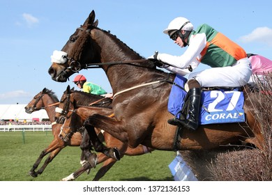 AYR RACECOURSE, AYRSHIRE, SCOTLAND, UK : 13 APRIL 2019 : Racehorse Doing Fine ridden by jockey Sean Bowen jumps a fence whilst running in the 2019 Scottish Grand National