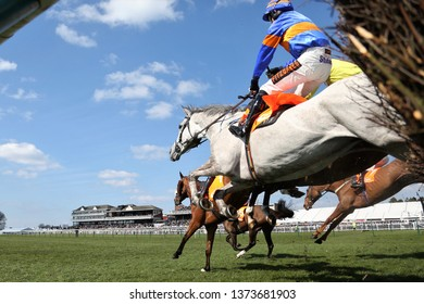 AYR RACECOURSE, AYRSHIRE, SCOTLAND, UK : 13 APRIL 2019 : The excitement and thrill of racehorses with their jockeys landing on the ground after jumping over a steeplechase fence at Ayr Races
