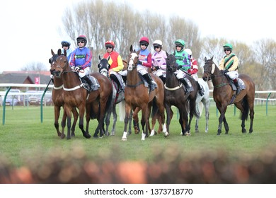 AYR RACECOURSE, AYRSHIRE, SCOTLAND, UK : 12 APRIL 2019 : A group of racehorses with their jockeys in the saddle make for a colourful sight as they circle at the Start before racing at Ayr Racecourse