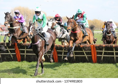 AYR RACECOURSE, AYRSHIRE, SCOTLAND, UK : 12 APRIL 2019 : Racehorses jump a hurdle at Ayr Races  - the winner is Theatre Legend ridden by Sean Quinlan in white with red cross belt and green sleeves
