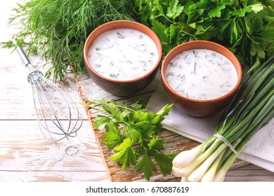 Ayran with fresh herbs - parsley, dill and green onion in clay bowls. Traditional Turkish yoghurt drink on wooden table.