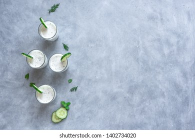 Ayran, homemade yogurt drink (kefir, lassi) with herbs and cucumbers - healthy summer refreshing cold drink, top view, copy space.