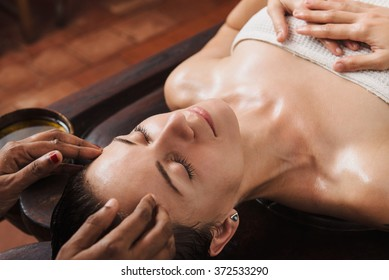 Ayurveda face massage with oil on the wooden table in traditional style made by asian women.