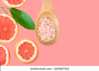 Ayurveda face skin scrub ingredients Himalayan salt in wooden spoon sliced grapefruit green leaf on cherry pink background. Beauty face care natural organic cosmetics concept
