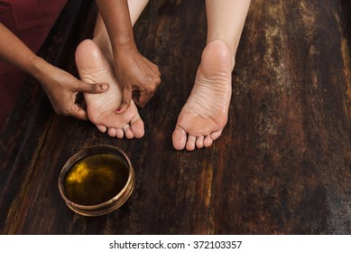 Ayurveda foot massage with oil on the wooden table in traditional style made by asian women. Top view.