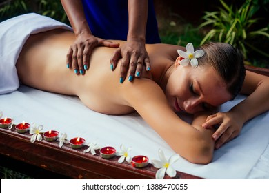 Ayurveda indian woman having relaxing body asia spa treatment india flowers and candles