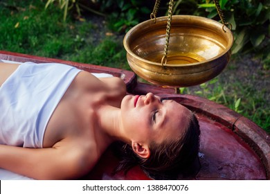ayurveda massage alternative healing therapy.beautiful caucasian female getting shirodhara treatment lying on a wooden table in India salon