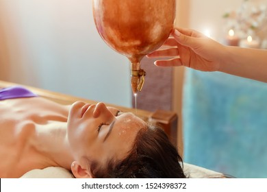 ayurveda massage alternative healing therapy.beautiful caucasian female getting shirodhara treatment lying on a wooden table in India salon.