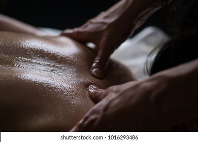 Ayurveda Massage concept. Beautiful young woman reciving relxing Massage of Her Oiled Back from Professional Masseur