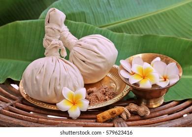 Ayurveda massage powder pads with flowers on metal plate, rotang table  and banana leaves