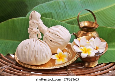 Ayurveda massage powder pads with flowers on metal plate, rotang table  and banana leaves