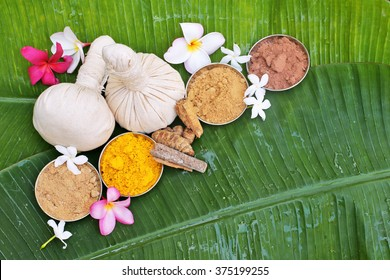 Ayurveda pads with powders, flowers on banana leaves . top view