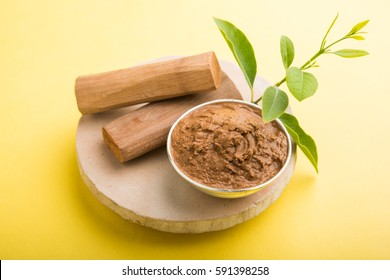 Ayurvedic Chandan powder or sandalwood paste in silver bowl with sticks and leaves placed over sahan or sahana or circular stone base for creating paste