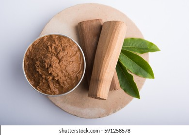 Ayurvedic Chandan or sandalwood paste in silver bowl with sticksand leaves placed over sahanor sahana or circular stone base for creating paste