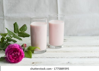 Ayurvedic drink pink milk or matcha. A two glass of refreshing cocktail stands on a wooden white background. Nearby lies a lilac rose