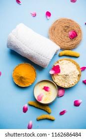 Ayurvedic face pack/mask using Gram Flour/besan, Haldi & milk ubtan placed in brass bowls with rose petals, scrub  and white napkin. selective focus