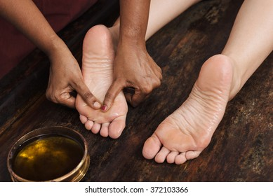 Ayurvedic foot massage with oil on the wooden table in traditional style made by asian women. Top view.