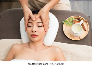 Ayurvedic Head Massage Therapy on facial forehead Master Chakra Point of Mix Race Caucasian Asian woman, Therapist Spa body woman hands treatment on customer to increase circulation release tension