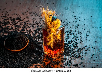 AYURVEDIC HERB i.e. Kalonji,black caraway seeds with its beneficial and essential oil on a brown surface in dark Gothic colors.This oil is used in weight loss,lowing the blood sugar/diabetes etc.