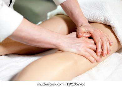Ayurvedic massage therapist working on the legs of a woman greased with scented and warm oil pleasure