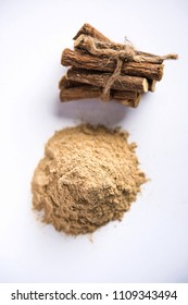 Ayurvedic Mulethi or Liquorice root stick or jeshthamadh powder served in a bowl over moody background
