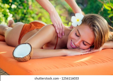 Ayurvedic relaxing massage ,health beauty happy closed eyes woman in spa salon getting massage on the holiday beach.Beautiful girl enjoying day spa resort, lying down on the table treatment procedure